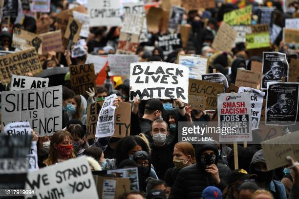 TOPSHOT Protesters hold placards as they attend a demonstration in Parliament Square in central London on June 6 to show solidarity with the Black...