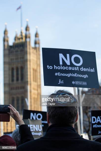 Protesters hold placards as they demonstrate in Parliament Square against antiSemitism on March 26 2018 in London England The Board of Deputies of...