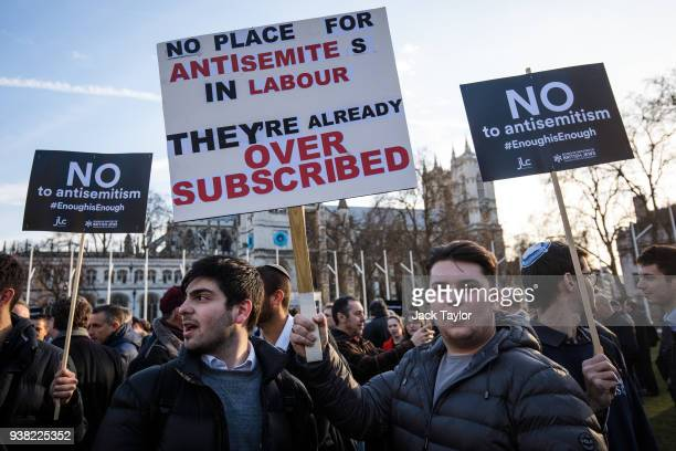 Protesters hold placards as they demonstrate in Parliament Square against antiSemitism in the Labour Party on March 26 2018 in London England The...
