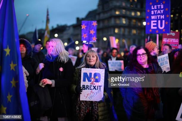 Protesters hold placards as they demonstrate on the day that MPs vote on Theresa May's Brexit deal, in Parliament Square on January 15, 2019 in...