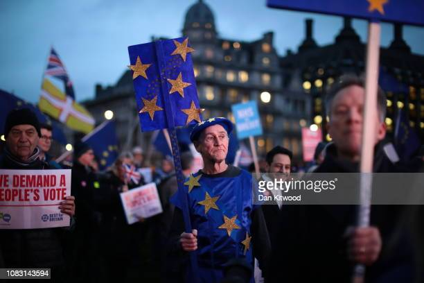 Protesters hold placards as they demonstrate on the day that MPs vote on Theresa May's Brexit deal outside the House of Commons on January 15 2019 in...