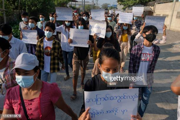 Protesters hold placards as they march during a demonstration against the military coup in Mandalay on May 11, 2021.