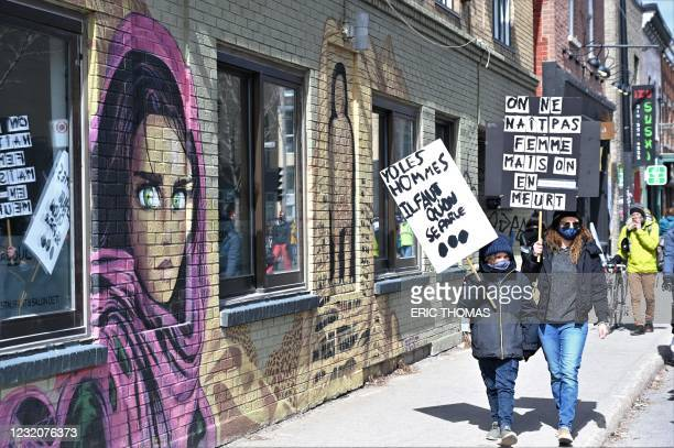 Protesters hold placards as they march in central Montreal on April 2, 2021 to protest against a rise in femicides in Quebec. - Eight women were...