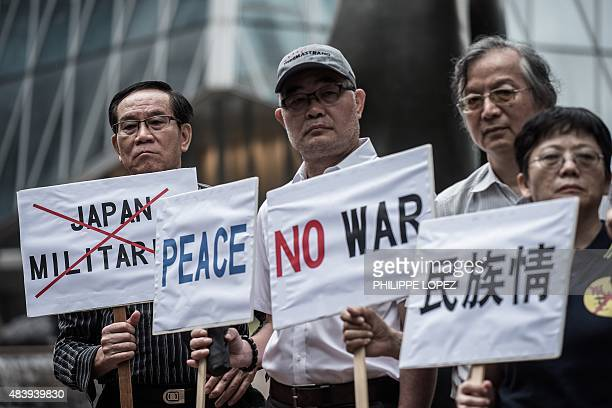 Protesters hold placards as they protest outside the Japanese consulate in Hong Kong on August 14 2015 on the day that Japanese Prime Minister Shinzo...