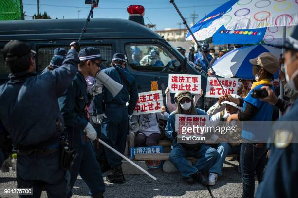 Protesters hold placards as they stage a sit in to block construction vehicles working on the expansion of Camp Schwab a United States military base...
