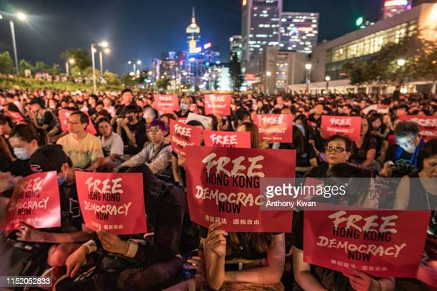 Protesters hold placards as they take part in a rally against the extradition bill ahead of 2019 G20 Osaka summit at Edinburgh Place in Central...