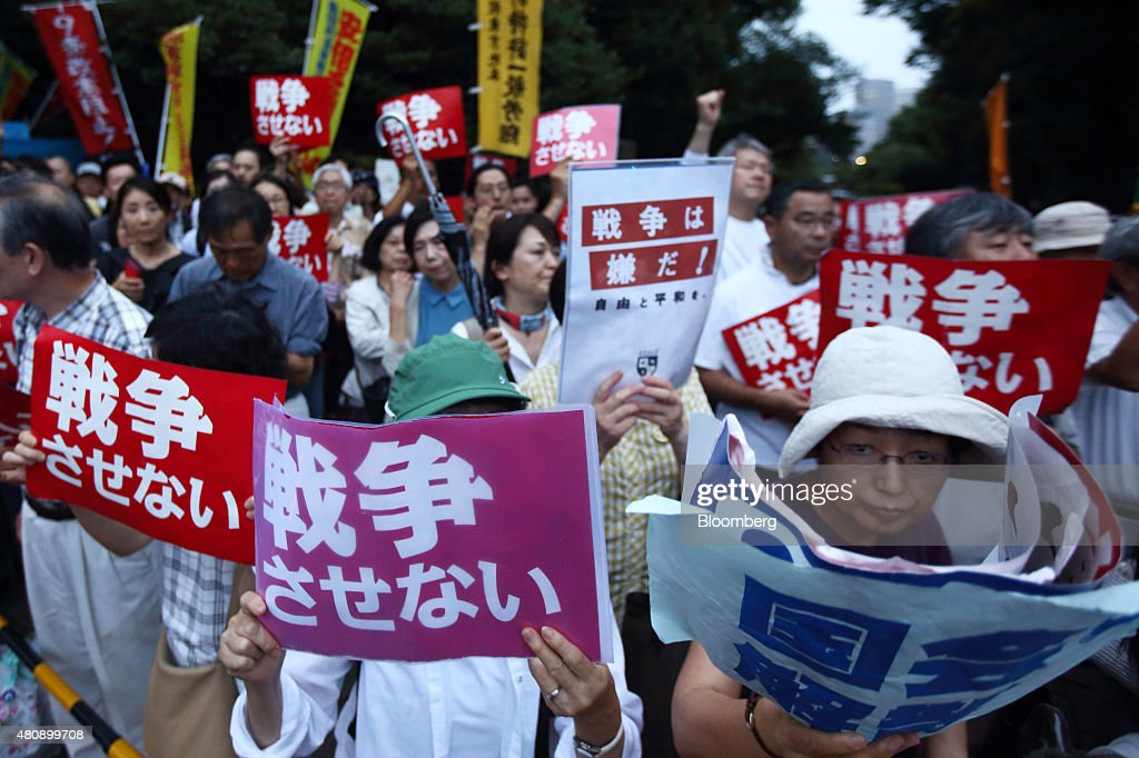 Protesters hold placards as they take part in a rally against the security bills outside the National Diet building in Tokyo, Japan, on Thursday, July 16, 2015. Japanese Prime Minister Shinzo Abe's security bills passed parliament's lower house Thursday after a night of noisy protests, as his push to expand the role of the military risks further eroding his public support. Photographer: Tomohiro Ohsumi/Bloomberg via Getty Images