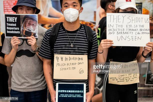 Protesters hold placards at Hong Kong's international airport following a protest against the police brutality and the controversial extradition bill...