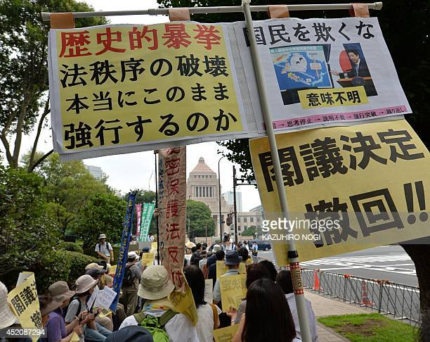 Protesters hold placards demanding the withdraw of the cabinet decision and shout antiAbe government slogans during a rally in front of the...