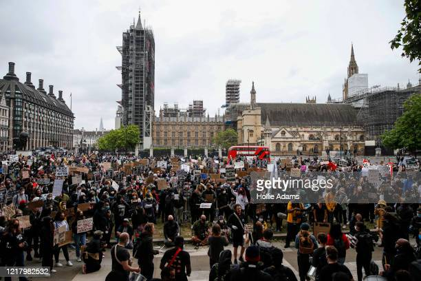 Protesters hold placards during a Black Lives Matter demonstration in Parliament Square in central London on June 6, 2020 in London, United Kingdom....