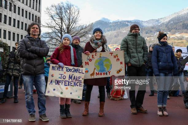 Protesters hold placards during a climate strike demonstration ahead of the World Economic Forum in Davos at Landquart railway station in Landquart...