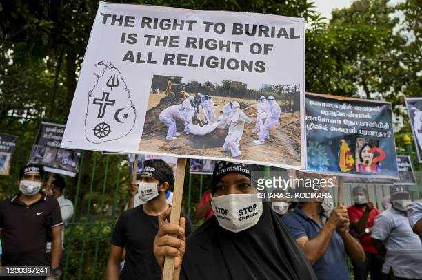 Protesters hold placards during a demonstration against the government policy of forced cremations of Muslims who died of the Covid-19 coronavirus,...