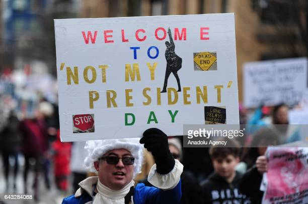 Protesters hold placards during a protest against President Trump and his policies in a demonstration called Not My President's Day organized by...