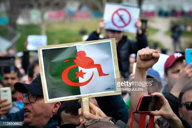 TOPSHOT Protesters hold placards during a sitin against the Algerian president's bid for a fifth term in office on March 3 2019 at the Porte d'Aix in...