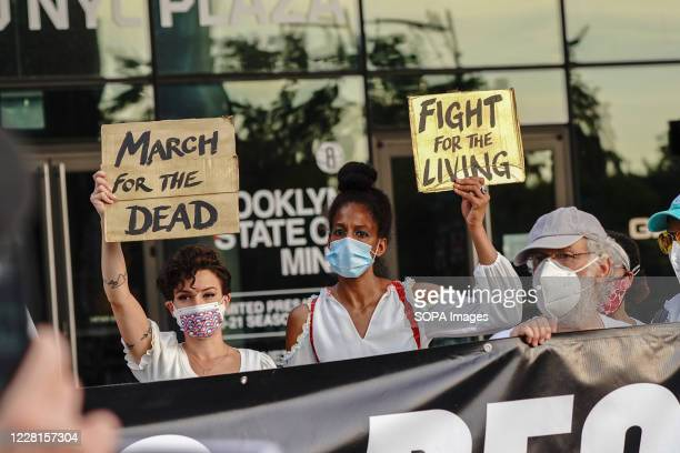 Protesters hold placards during the demonstration Families grieving the loss of their loved ones by the pandemic organized a 'March for the Dead' in...
