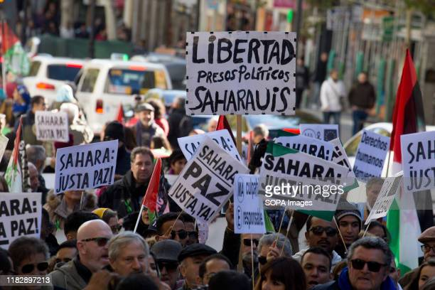 Protesters hold placards during the demonstration. Thousands of Saharawis arrive from all over Spain to demand the end of Morocco's occupation in...