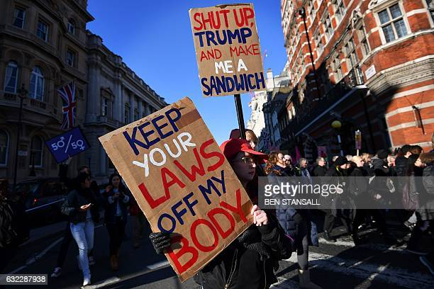 Protesters hold placards during the Women's March in London on January 21, 2017 as part of a global day of protests against new US President Donald...