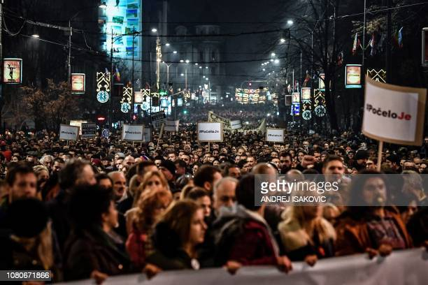 Protesters hold placards reading 'It started' during a demonstration of thousands of people against the Serbian president in the capital Belgrade on...