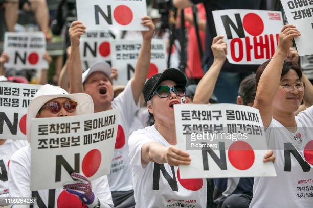 Protesters hold placards reading 'No Abe' during a demonstration against Japan's removal of South Korea from a list of trusted trading partners in...