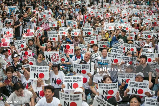 Protesters hold placards reading 'No Abe!' during a demonstration against Japan's removal of South Korea from a list of trusted trading partners in...