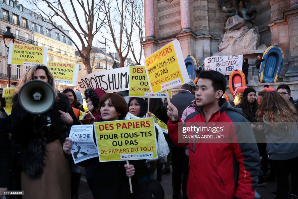 Protesters hold placards reading 'Papers for all or no papers at all' on the Place Saint-Michel in Paris on February 21, 2018, during a demonstration against the French government's new immigration bill. The French government defended a new immigration bill as 'completely balanced' on February 21 despite criticism from rights groups and some ruling party lawmakers that it will lead to thousands of extra deportations. The draft law, which criminalises illegal border crossings and speeds up procedures to deport economic migrants, was presented to the cabinet of President Emmanuel Macron for the first time. PHOTO / Zakaria ABDELKAFI