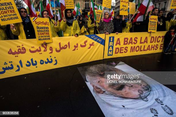 Protesters hold placards reading 'Support Iranians risen up against the religious dictatorship' as they stand behind a portrait of Iranian President...