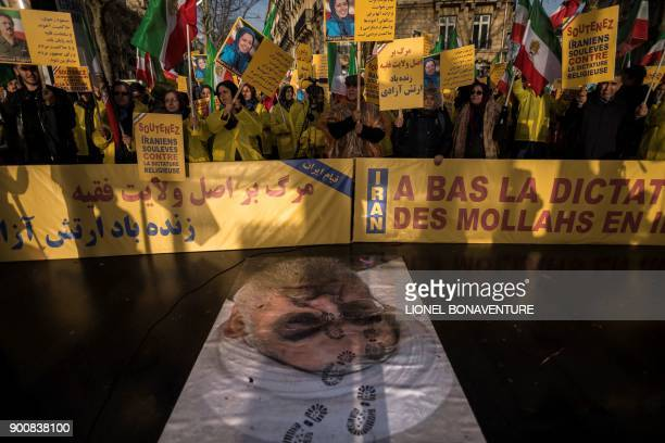 TOPSHOT Protesters hold placards reading 'Support Iranians risen up against the religious dictatorship' as they stand behind a portrait of Iranian...