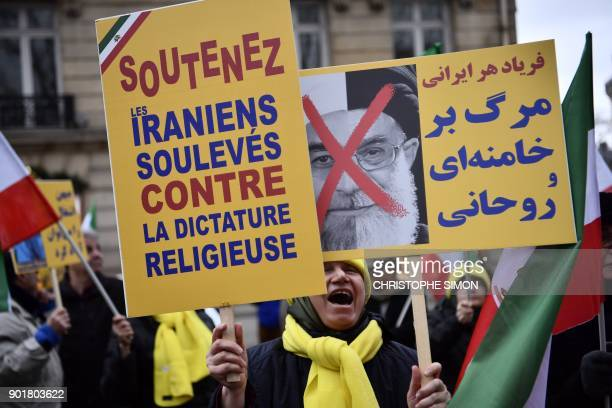 Protesters hold placards reading 'Support Iranians risen up against the religious dictatorship' and a portrait of Iranian President Hassan Rouhani...