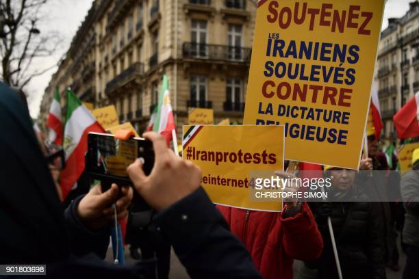 Protesters hold placards reading 'Support Iranians risen up against the religious dictatorship' during a demonstration in support of the Iranian...