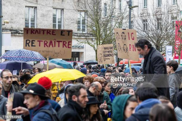 Protesters hold placards relating to the French government's contested pensions overhaul one depicting French President Emmanuel Macron saying...