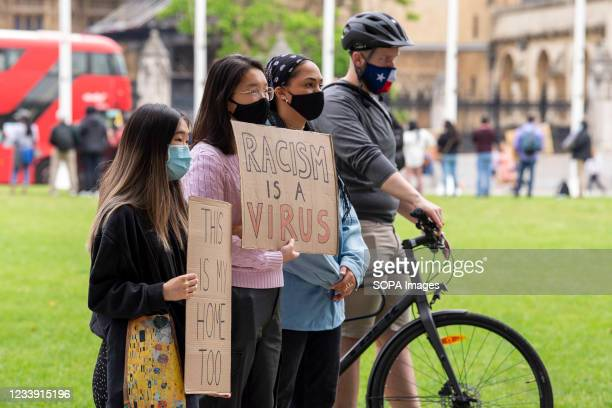 Protesters hold placards saying Racism is a virus and This is my home too during a Stop Asian Hate protest at Parliament Square in London. Anti-Asian...