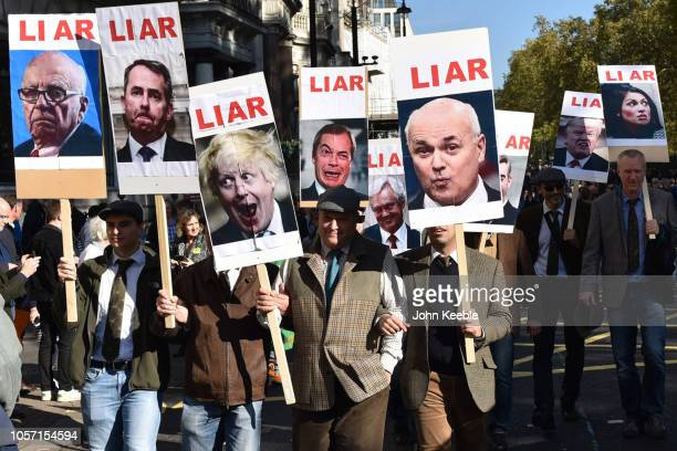Protesters hold placards showing images of Boris Johnson Iain Duncan Smith Nigel Farage David Davis and Donald Trump with the word Liar march to...