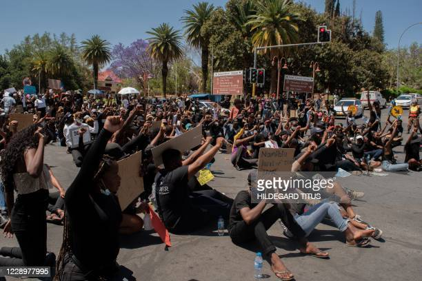 Protesters hold placards while they gesture during the second day of the #ShutItDown Protests, where hundreds of Namibian youth protested against...