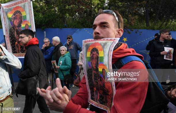 Protesters hold posters depicting the Virgin Mary with a rainbow halo during a rally for freedom of speech in downtown Warsaw on May 7 2019 after a...