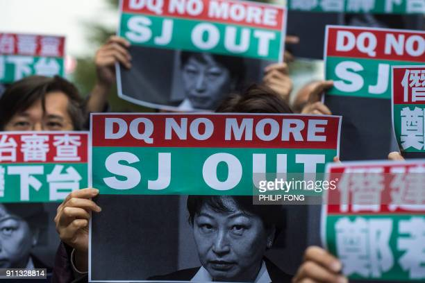 Protesters hold posters of Teresa Cheng the secretary for Justice during a protest at the Central Givernment Complex in Hong Kong on Januray 28 2018...