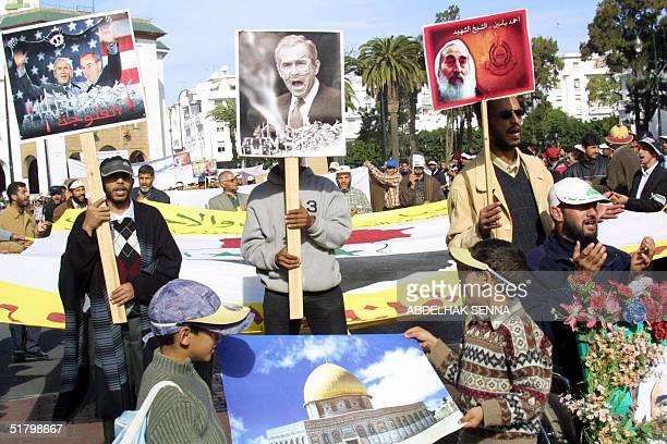 Protesters hold posters showing US President George W. Bush and Al-Qaeda leader Osama bin Laden , 28 November 2004 in Rabat, during a demonstration...