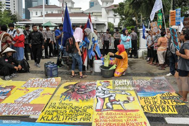 Protesters hold posters to protest against water privatization in front of City Hall in Jakarta Indonesia on March 22 2018 This action was held to...