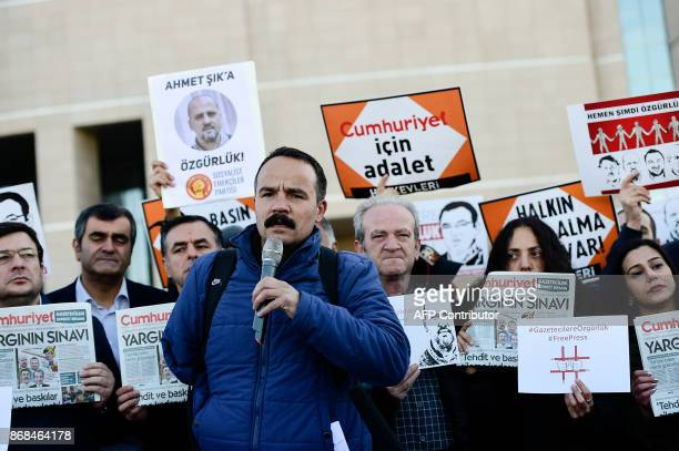 Protesters hold posters with images of Turkish daily newspaper Cumhuriyet staff members during a demonstration in front of a courthouse in Istanbul...