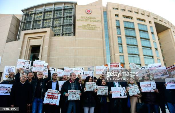 Protesters hold posters with images of Turkish daily newspaper Cumhuriyet staff members and copies of the newspaper during a demonstration in front...