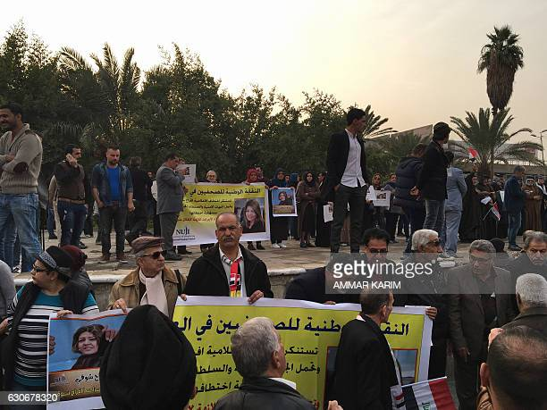 Protesters hold protraits of Iraqi female journalist Afrah Shawqi during a demonstration calling for her release on December 30 in Baghdad's Tahrir...