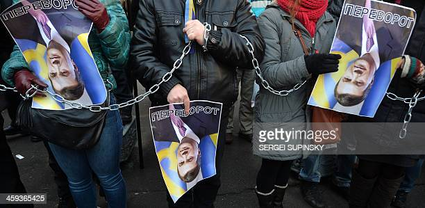 Protesters hold rotated pictures of Ukrainian President Viktor Yanukovych and signed 'Upside down ' during the protest action at the Internal Affairs...