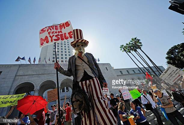 "Protesters hold signs after a march to Los Angeles City Hall during the ""Occupy Los Angeles"" demonstration in solidarity with the ongoing ""Occupy..."