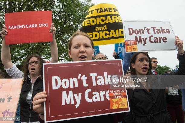 Protesters hold signs and shout at lawmakers walking out of the US Capitol in Washington DC on May 4 2017 after the House of Representatives narrowly...