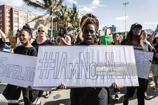 Protesters hold signs and shout slogans as they take part in a march against gender based violence and in solidarity with women who have been subject...