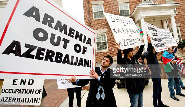 Protesters hold signs and shout slogans during a protest across the street from the Armenian Embassy in Washington DC on February 24 2012 The...