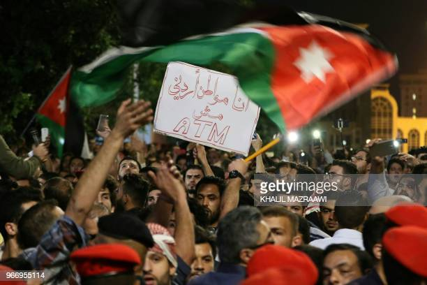 Protesters hold signs and wave flags near Jordanian security forces during a demonstration outside the prime minister's office in the capital Amman...