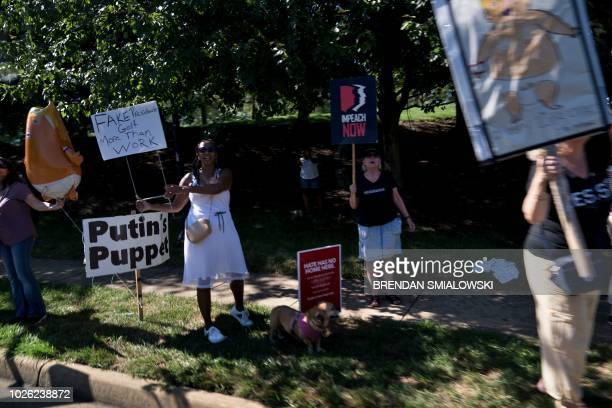 Protesters hold signs as a motorcade with US President Donald Trump departs the Trump National Golf Club September 2 2018 in Sterling Virginia