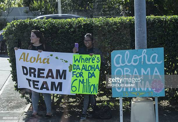 Protesters hold signs as the motorcade of US President Barack Obama leaves his vacation residence in Kailua on January 3 2015 on the last day of his...