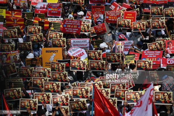 Protesters hold signs as they block a road during a demonstration against the military coup in Yangon on February 17, 2021.