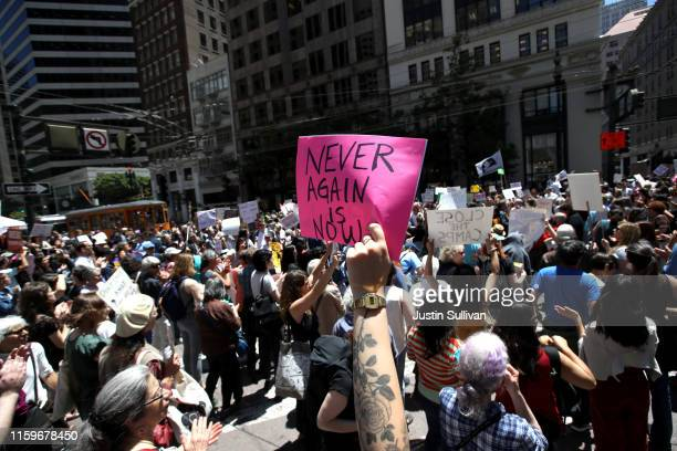 Protesters hold signs as they block a street in front of US Sen Dianne Feinstein's office during a demonstration against migrant detention facilities...